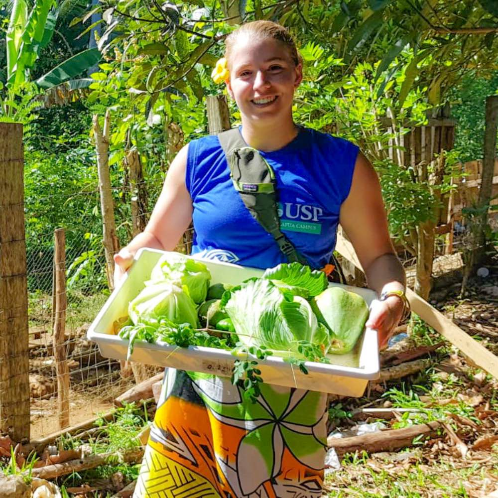 SIT student carrying fresh vegetables at organic farm