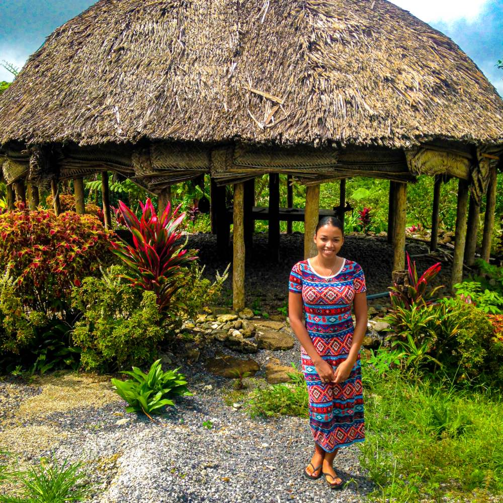 Smiling girl in front of gazebo with straw roof